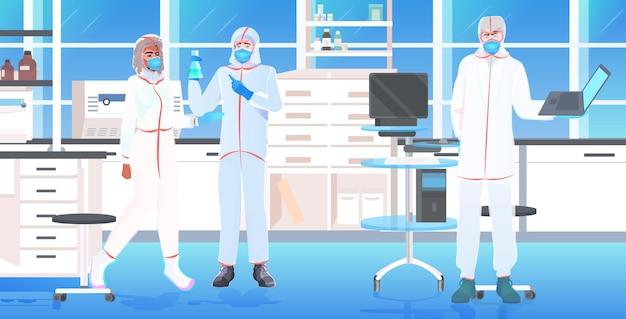 Das ärzteteam, das reagenzgläser mit coronavirus-zellen hält, kämpft gegen covid-19