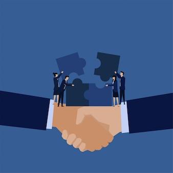 Das business flat team hat das puzzle über der handshake-metapher von teamwork und kooperation gesetzt.