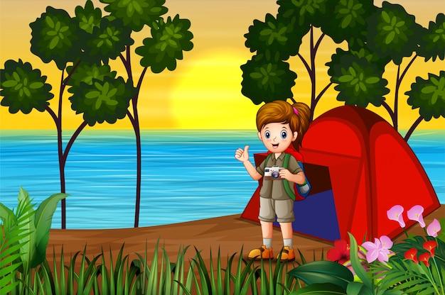 Das entdeckermädchen auf campingplatz an der sonnenunterganglandschaft