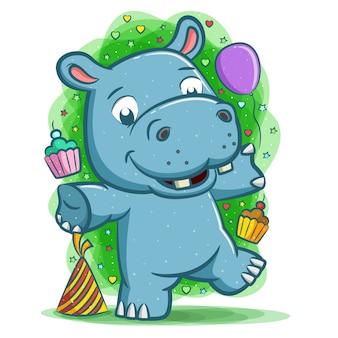 Das fröhliche nilpferd feiert die party mit ballon und kuchen
