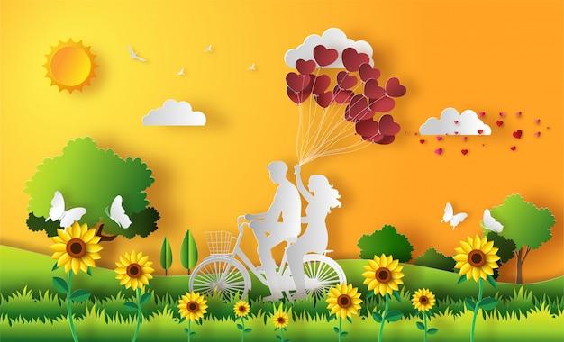 Das glückliche paar, das entlang auf berg mit einer hand reitet, die herz hält, formte ballone.