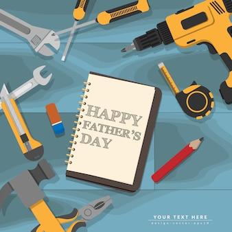 Das glückliche vatertagsschreiben des textes im notizbuch lag auf hölzernem schreibtisch des blauen mechanikers mit gelben hauptreparaturwerkzeugen