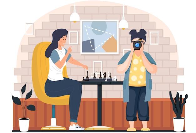 Das junge mädchen des fotografen macht abends fotos von einer frau, die schach in gemütlicher wohnzimmeratmosphäre spielt. charakter hält eine figur und macht am wochenende einen zug, hobby, wettbewerb, logikspiel