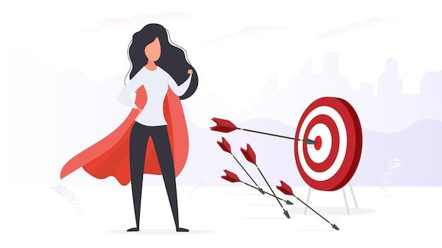 Das mädchen mit dem roten mantel trifft das ziel. großes ziel. ein pfeil, der die mitte des ziels trifft. superhelden-frau. vektor.