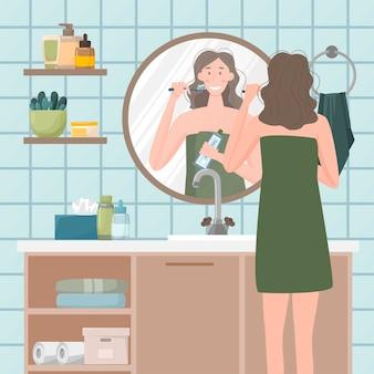 Das mädchen putzt sich vor dem badezimmerspiegel die zähne