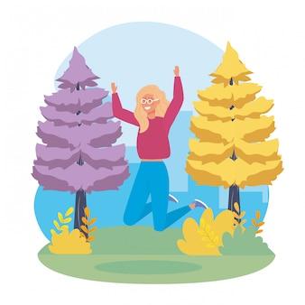 Das mädchen springend mit zufälliger kleidung und kiefernbäumen