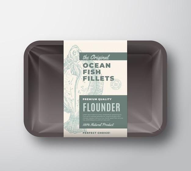 Das original-fischfilet-etikett mit abstrakter verpackung auf kunststoffschale mit zellophanabdeckung. moderne typografie und handgezeichnete flunder plattfisch silhouette hintergrund layout.