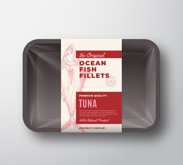 Das original-fischfilet-etikett mit abstrakter verpackung auf kunststoffschale mit zellophanabdeckung. moderne typografie und handgezeichnete thunfisch-silhouette-hintergrundlayout. isoliert.