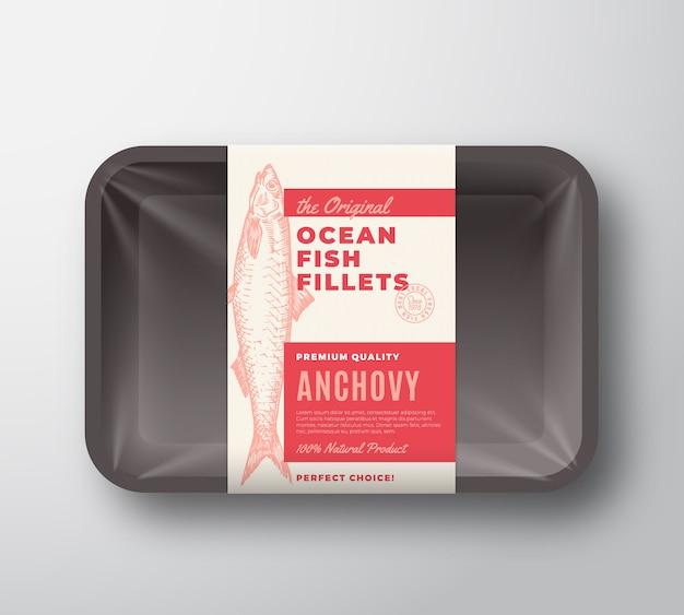 Das original-fischfilet-etikett mit abstrakter verpackung auf kunststoffschale mit zellophanabdeckung. moderne typografie und handgezeichnetes sardellenschattenbild-hintergrundlayout. isoliert.
