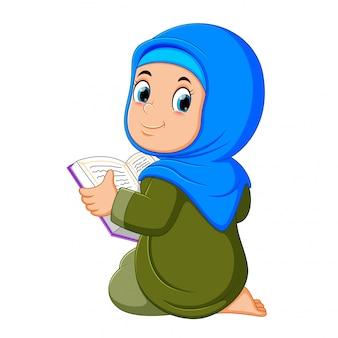 Das schöne mädchen mit blauem schleier hält al quran