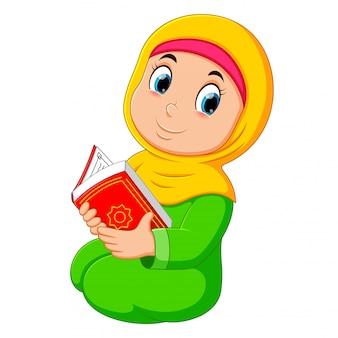 Das schöne mädchen mit gelbem schleier hält al quran