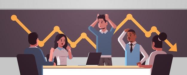 Das wirtschaftlerteam, das über das fallen des wirtschaftlichen diagrammpfeiles frustriert wurde, fallen finanzkrise bankrotte investitionsrisikokonzept-mischungsrennen betonte die angestellten, die am horizontalen porträt des runden tisches sitzen