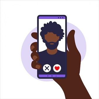 Dating app. mobile dating app zum finden neuer freunde, kontakte und romantischer partner. illustration der menschlichen hand, die smartphone mit foto afrikanischer mann hält. abbildung in wohnung.