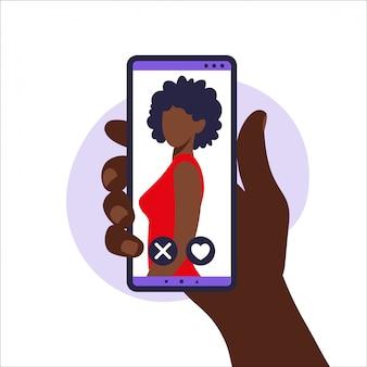 Dating app. mobile dating app zum finden neuer freunde, kontakte und romantischer partner. illustration der menschlichen hand, die smartphone mit foto afrikanisches mädchen hält. abbildung in wohnung.