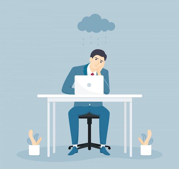 Deprimierter und müder geschäftsmann, der am schreibtisch im kreativen büro sitzt.