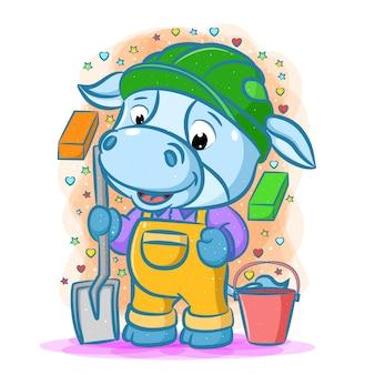 Der cartoon der blauen baumeisterkuh unter verwendung der grünen helmhalteschaufel