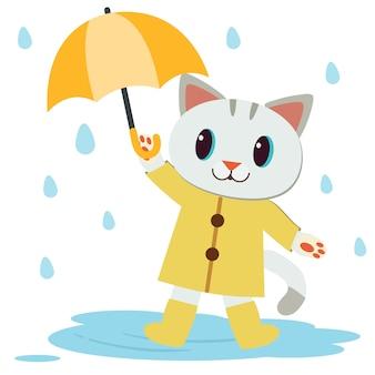 Der charakter der niedlichen katze trägt den gelben regenmantel und die stiefel und hält einen regenschirm.