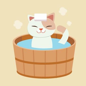 Der charakter der süßen katze nimmt ein japanisches thermalbad. die katze nimmt ein onsen. es sieht glücklich und entspannend aus. katze, die in einem fass in einem bad im freien badet.
