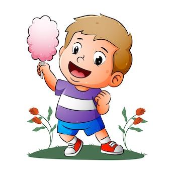 Der fröhliche junge hält die große farbige zuckerwatte der illustration