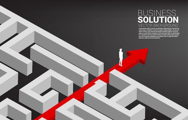 Der geschäftsmann, der auf rotem pfeilweg steht, brechen vom labyrinth aus. geschäftskonzept zur problemlösung und lösungsstrategie.