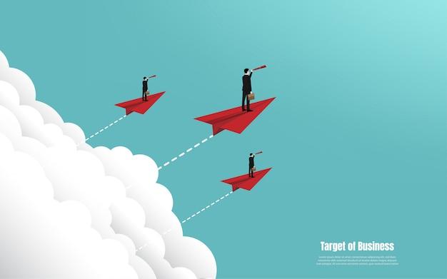 Der geschäftsmann, der binokularen stand auf papierflugzeugfliegen hält, gehen zum erfolg