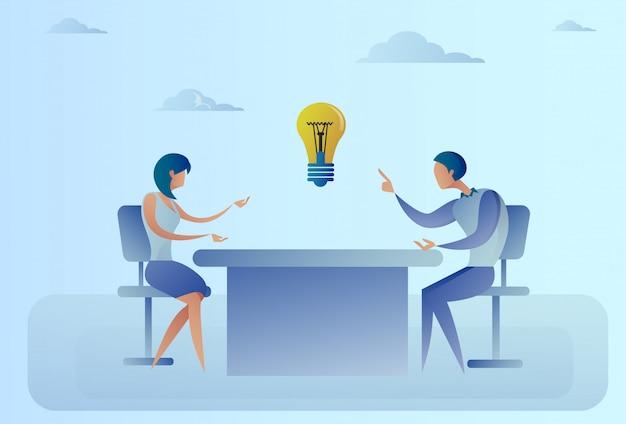 Der geschäftsmann und frau, die am schreibtisch sitzen, besprechen neue kreative ideen-konzept-glühlampe