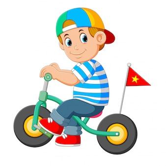 Der junge benutzt die mütze und spielt mit dem kleinen fahrrad
