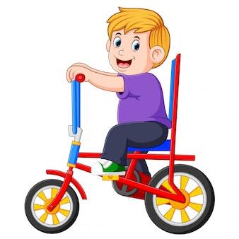 Der junge fährt mit dem bunten fahrrad
