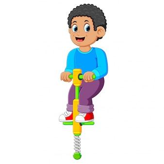 Der junge spielt mit dem springstock mit dem glücklichen gesicht