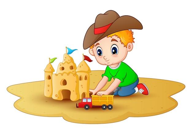 Der kleine junge, der eine sandburg mit einem auto bildet, spielt am strand