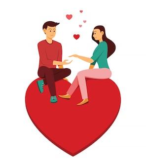 Der liebhaber mann und frau sitzen auf dem großen herzen ist symbol der liebe.