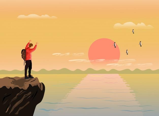Der mann stand auf und zeigte glücklich seine hände auf dem gipfel des berges
