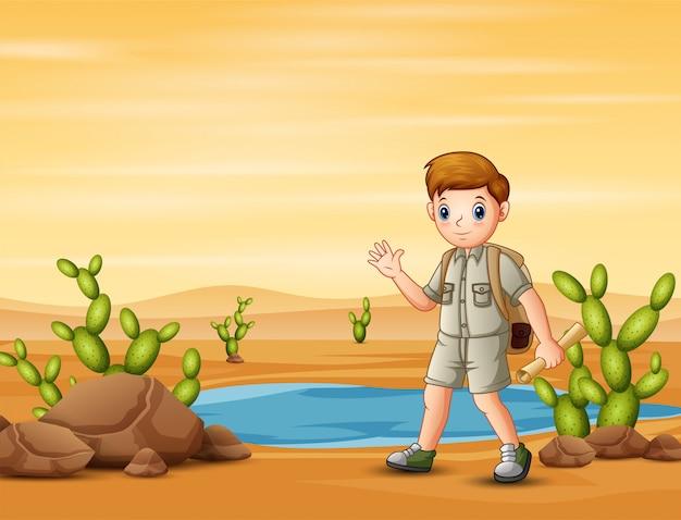 Der pfadfinderjunge, der im wüstenfeld mit karten wandert