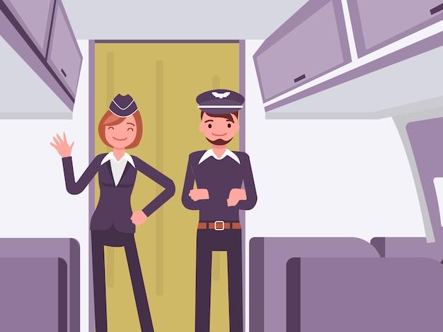 Der pilot und der flugbegleiter posieren in der flugzeugkabine