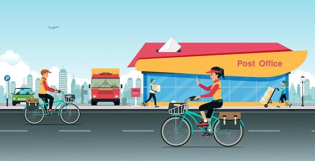 Der postbote fährt mit dem fahrrad vor einem postamt
