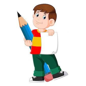 Der schlaue junge hält das papier und den großen bleistift
