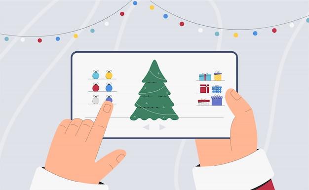 Der weihnachtsmann hält eine tafel mit einem weihnachtsbaum und kugeln und girlanden auf dem bildschirm.