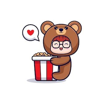 Design des niedlichen mädchens, das bärenkostüm umarmt großes popcorn trägt