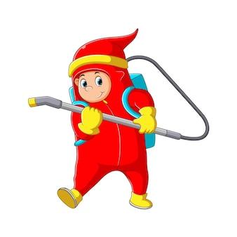 Die abbildung des jungen, der die spritzpistole hält und die rote persönliche schutzausrüstung verwendet