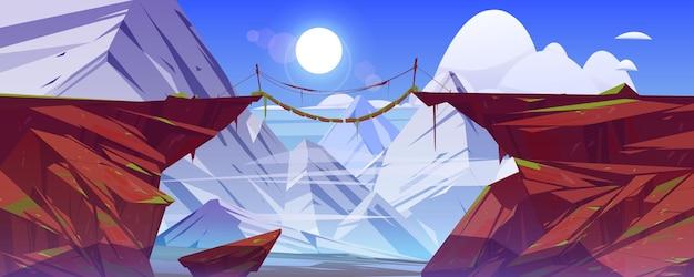 Die brücke zwischen den bergen hängt über der klippe in der landschaft der schneebedeckten felsgipfel