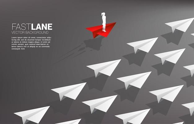 Die geschäftsfrau, die auf rotem origamipapierflugzeug steht, ist bewegung schneller als gruppe weiß. geschäftskonzept der überholspur für das bewegen und das marketing