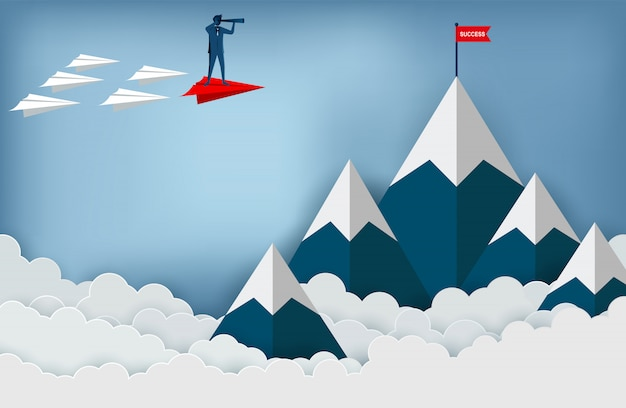 Die geschäftsmänner, die ferngläser auf einem roten papierflugzeug halten, gehen zum ziel der roten fahne auf bergen