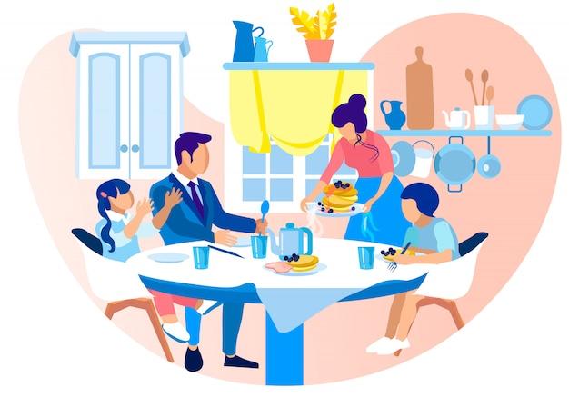 Die glückliche familie, die am tisch sitzt, essen geschmackvolles frühstück