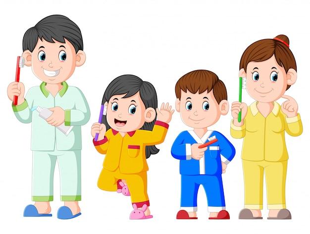 Die glückliche familie posiert mit der zahnbürste
