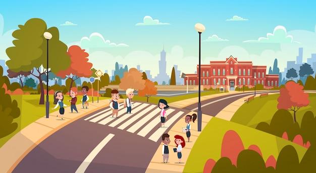 Die gruppe schüler, die auf crosswalk-mischungs-rennstudenten gehen, gehen zur schulüberfahrt-straße