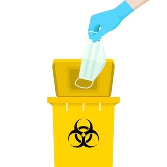 Die hand, die eine maske hält, befindet sich über dem gelben behälter mit dem symbol für infektiösen abfall.