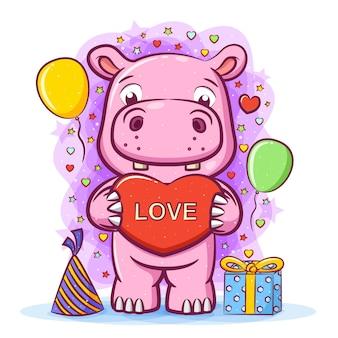 Die illustration des rosa nilpferds mit liebe auf seiner hand zum geburtstag