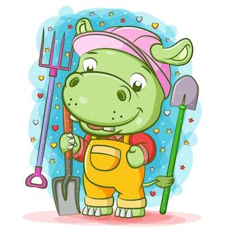 Die karikatur des grünen nilpferds hält zielfernrohr um utensilien