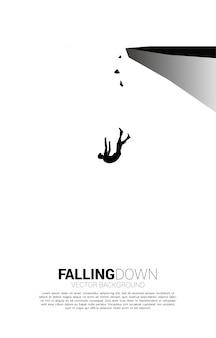 Die silhouette des geschäftsmannes rutscht aus und fällt von der klippe herunter. konzept für ausfall und versehentliches geschäft