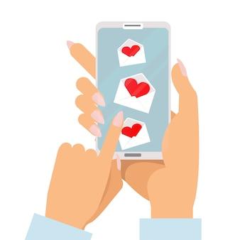Die zwei hände der frau mit der maniküre, die smartphone mit liebesmitteilungen auf schirm hält.